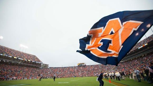 Auburn cheerleader waves a flag during the NCAA football