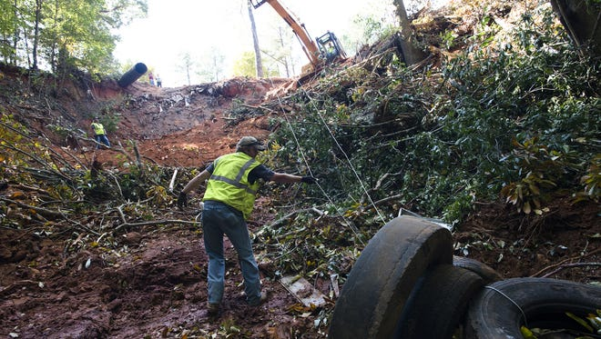 Shane Wright, C.W. Owens Enterprises employee, helps clean out tires from a ravine on Autauga County 22 on Oct. 9, 2014. The Alabama Department of Environmental Management said last week legislators forced them to transfer money out of a fund that helps dispose of tire dumps.