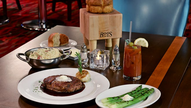 A rib eye, garlic potatoes and asparagus; along with a Bloody Mary.