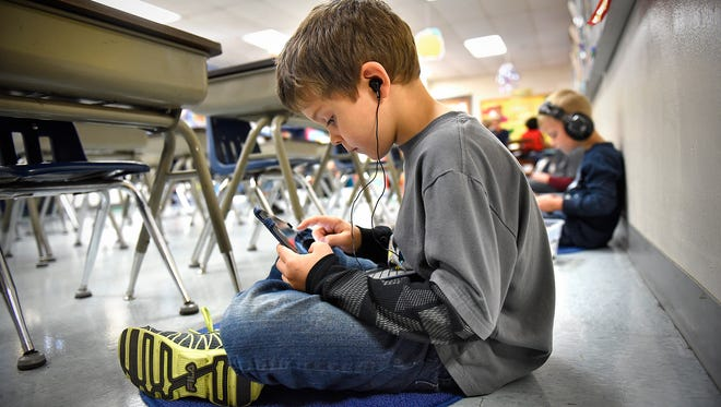 St. Cloud Christian School first-grade students use iPads while completing a learning exerciseTuesday in class.