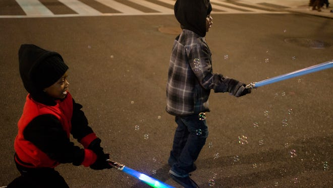 Desamuel King, 4, left, and his cousin TJ Sellers swing at bubbles with light saber's during the Montgomery Christmas Parade on Friday, Dec. 18, 2015, in Montgomery, Ala.