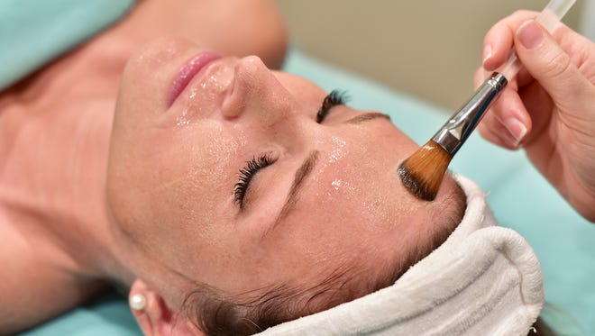 Application of a Brightening Pomegranate Exfoliating Treatment at Escape Wellness Spa.