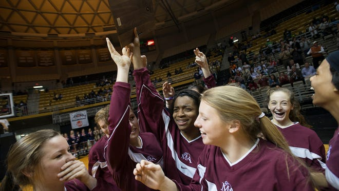 Montgomery Academy's Kayla White (22), center, holds up the Central Region Championship trophy with the rest of their team after the AHSAA Regional Final at the Dunn-Oliver Acadome in Montgomery, Ala.