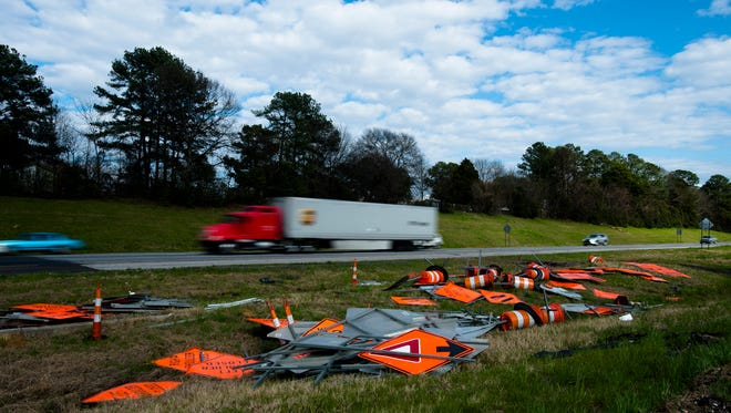Signs from a construction zone lay in a pile on Interstate 85.