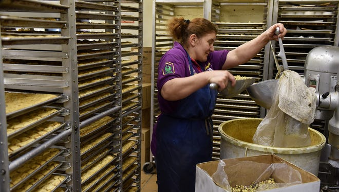 Nadia Ghlyana grinds pistachios for baklava at Mid-East Pastry Delight in Sterling Heights.