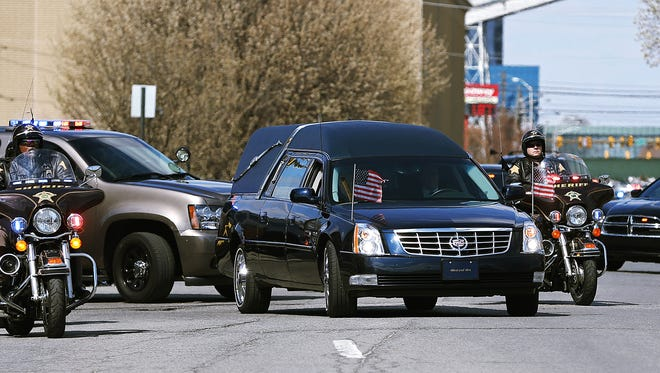 The body of Howard County Deputy Carl A. Koontz is accompanied by a police escort during transportation to Kokomo, Monday, March 21, 2016, at the  Marion County coroner's office, downtown Indianapolis, Ind.