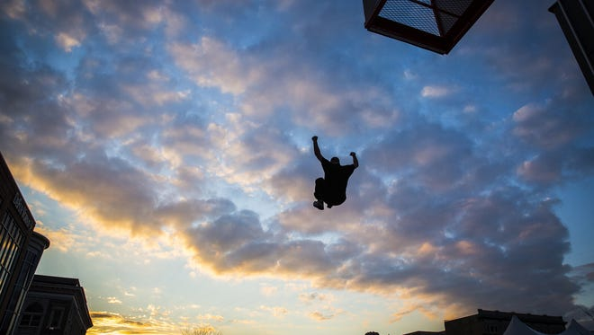 A man leaps onto an inflatable at an outside attraction during Muncie Gras. Officials cited the jump as a popular attraction.