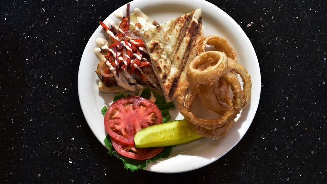 A grilled Gulf grouper sandwich with spicy mayo, peppers and onions on a grillled pita, $14, at Skopelos.