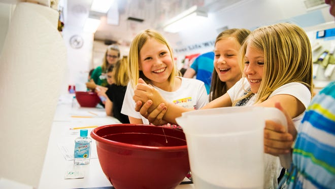 West Manheim Elementary third grade students from left, Jordyn Lauer and Maddy Long, watch as Kassidy Rebert washes her hands in a bowl with soap and water while conducting an experiment inside the mobile AgLab on Tuesday at West Manheim Elementary. Students were hypothesising which method of washing your hands most effectively eliminates germs and bacteria.