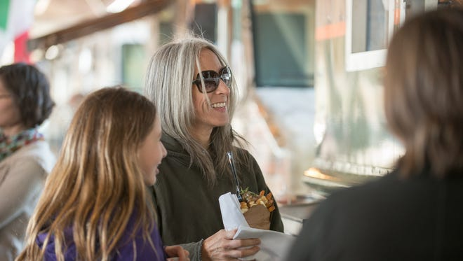 Kelly Collins of Macedon along with her daughter Autumn, 11, get food at Le Petite Poutine food truck Wednesday night.