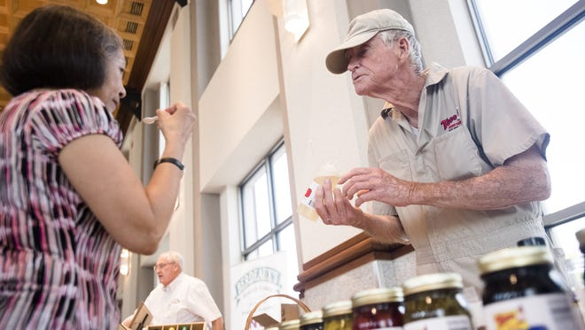 Minh Michaelson tastes some syrup as maker Joe Todd, Dothan, watches during the Alabama Tourism Department hosted Alabama Makers Market on June 4, 2015, at the RSA Activity Center in Montgomery.