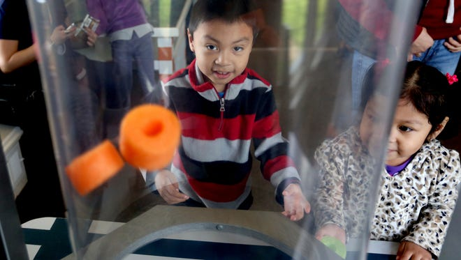 Erick Quirino and his sister, Leslie Quirino of Salem, play with a wind tube at the Gilbert House Children's Museum in February. The museum will have free admission June 27.