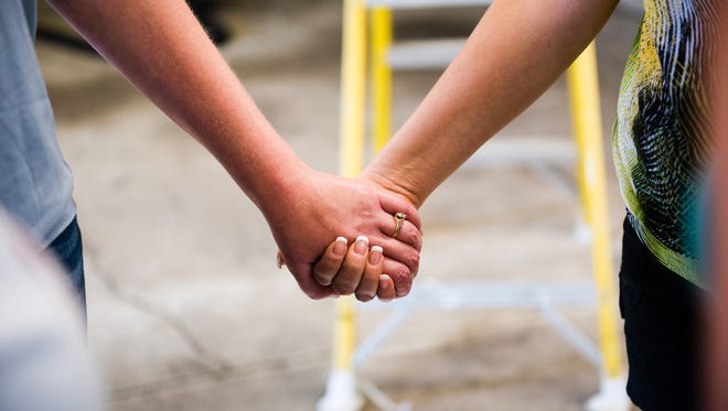 Kirsten Schaub and Juliet Sharrow hold hands during a prayer circle in June during preparation for a storefront for Love LIVES, a non-profit in Hanover. The organization, founded by Sharrow, will be dedicated to helping victims of sexual or domestic abuse.
