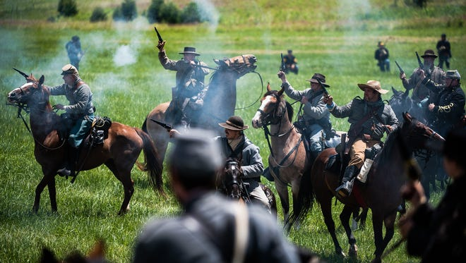 Re-enactors fire revolvers during a cavalry battle re-enactment in 2015 during the Battle of Gettysburg re-enactment.