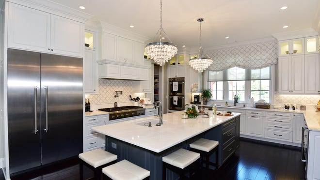 The kitchen was designed in grays and creams with accent lighting.