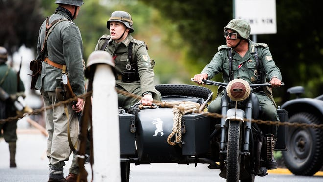 """German re-enactors """"occupy"""" a Netherlands village during a World War II re-enactment in New Oxford on Sept 17, 2016. The re-actment portrayed Operation Market Garden, an Allied airborne assault in the Netherlands on Sept. 17, 1944."""
