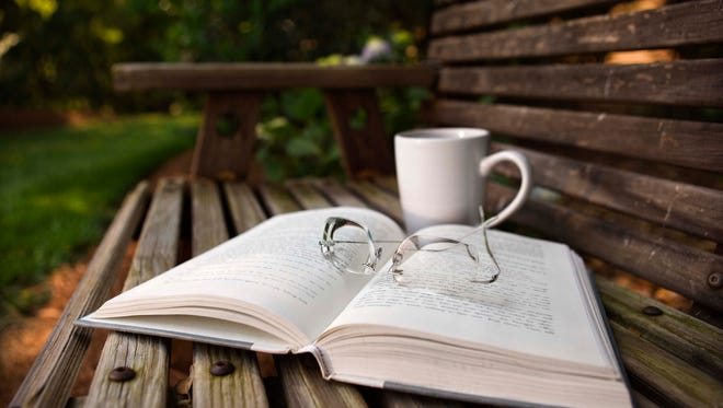 Still life of open book, eyeglasses and coffee cup on wooden bench.