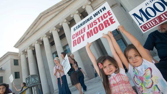 Noami Grace Thomas, 6, and Grace Nelson, 5, hold a sign in support of Roy Moore during the ethics trial of Alabama Chief Justice Roy Moore on Wednesday, Sept. 28, 2016, in Montgomery, Ala.