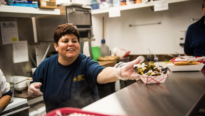 Concession stand manager Shelly Little with the Littlestown High School band boosters serves up a new concession stand item called the Bolt Nachos for a customer Friday night Sept. 30, 2016 at Littlestown High School before their football game against Delone.  The Bolt Nachos, featuring sour cream, cheese, jalapeños and yellow and blue nacho chips in honor of the team's colors started being sold last week during alumni weekend.