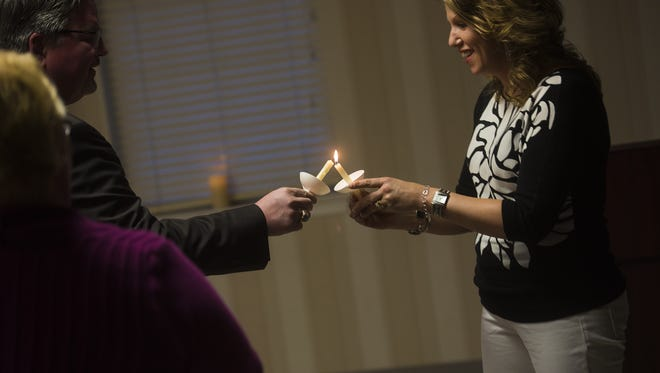 Juliet Sharrow lights the candle of Dana Ward, a detective with the York County District Attorney special case unit, during the Safe Home of Hanover YWCA candlelight vigil to commemorate National Crime Victims' Rights Week in April.