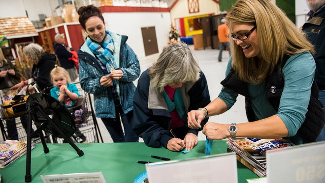Liz Johnides, at right, who's family owns The Markets at Hanover, helps customers enter for a drawing to win a mystery bag of goodies at the customer appreciation booth Saturday Nov. 26, 2016 at The Markets at Hanover during Small Business Saturday.