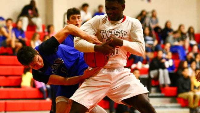 West Oso's Kwamin Huff pulls the ball out of the hands of Ingleside's Michael Smith during the first quarter of their game at West Oso on Tuesday, Jan. 3, 2017.