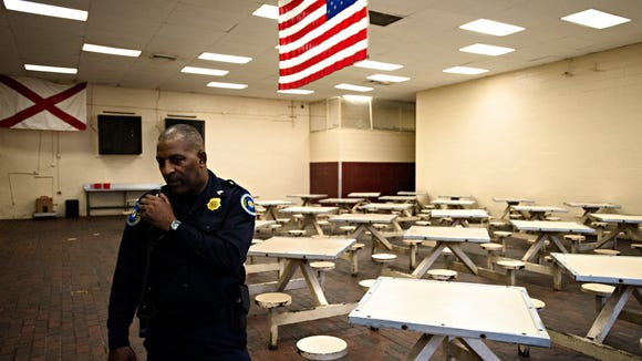 A corrections officer listens to his radio at Draper Correction Facility in Elmore County, Ala., on Monday, Feb. 6, 2017. Draper Correction Facility is the oldest correction facility in the state of Alabama. The prison opened in 1939. It is currently housing 1059 prisoners, Draper's designed capacity is 656.