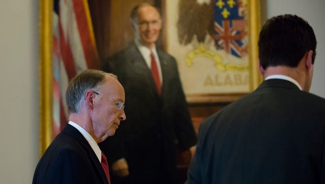 Alabama Governor Robert Bentley walks passed his portrait to his State of the State address on Tuesday, Feb. 7, 2017, at the Alabama Capitol building in Montgomery, Ala.
