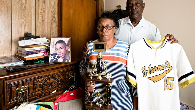 Thomas Earl Crossley holds his sons old ASU baseball jersey as his wife Helen Crossley holds his ASU MVP trophy while standing inside Brett Crossley's former room on Monday, Feb. 20, 2017, in Louisville, Ala. Brett Crossley was murdered in August of 1998 at 265 Park Town Way in Montgomery, Ala., his case has not been solved.