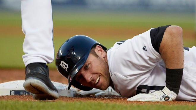 Detroit Tigers shortstop Andrew Romine (17) reacts after he dive back safe at first on a single in the third inning against the Seattle Mariners at Comerica Park.