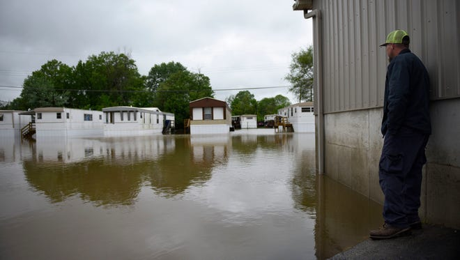 In this Wednesday, May 3, 2017 photo, James Smallwood stands next to floodwaters looking for a way to get a closer look at his flooded apartment in Pacific, Mo.