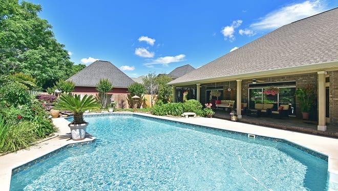5045 Avocet Lane, the lush, resort-like backyard pool area.