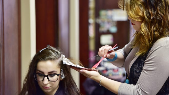 Kendall applies red color on client Katelyn Davis.