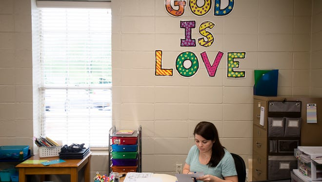 Marilee Hutchinson prepares her classroom for school Montgomery Christian School at the school's new location, 3265 McGehee in Wednesday, Aug. 9, 2017.
