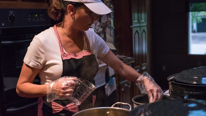Mykel Brawley, owner of the Fort Collins Pickle Company, prepares brine on the stovetop in her home kitchen on Thursday, August 10, 2017.