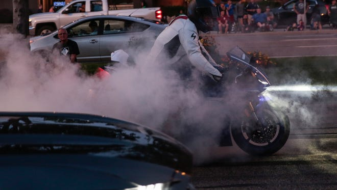 A motorcyclist does a burnout as he cruises down Woodward Avenue near Maple Road in Birmingham during the Woodward Dream Cruise, Saturday, August 19, 2017.
