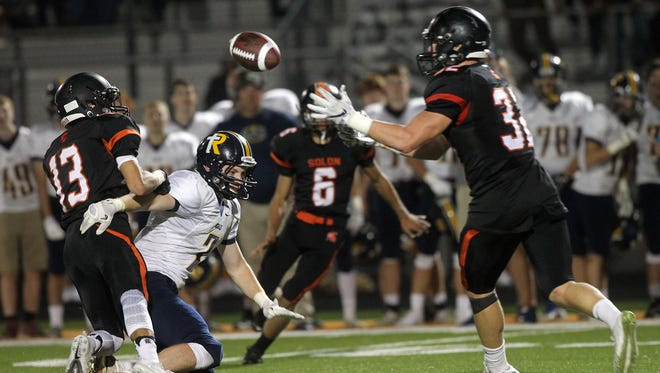 Solon's Adam Bock, right, intercepts a pass that he would run in for a touchdown during the Spartans' game against Regina in Solon on Friday, Sept. 1, 2017.