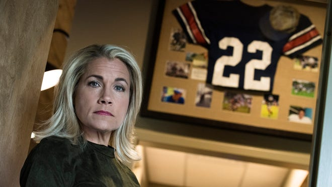 Rebecca Ellis stands in front of a picture frame containing pictures of her son, Cole Ellis, and his jersey on Tuesday, Sept. 12, 2017, in Montgomery, Ala. Cole Ellis committed suicide.