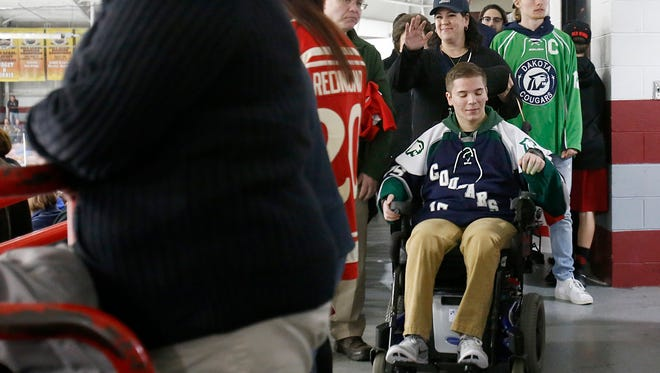 Sarahanne Mastronardi, waves to a friend while walking behind her son, Anthony Mastronardi, during a fundraising event for Anthony, on Sunday, April 30, 2017 at Fraser Hockeyland in Fraser. Mastronardi suffered a severe spinal cord injury during a high school hockey game in December 2016.