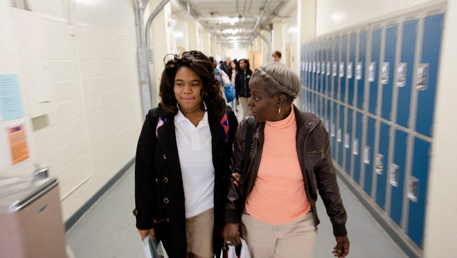Sharon Harris, a visual impairment specialist, walks Lindsey Towns from one class to another on Wednesday, Nov. 15, 2017, at BTW Magnet High School in Montgomery, Ala. Towns lost her eyesight before her 8th grade year and is legally blind.