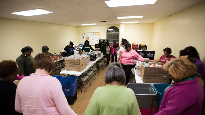 Volunteers pray before working for True Divine Baptist Church, which collects food for students in Brewbaker schools, on Thursday, Nov. 16, 2017, to bag food in Montgomery, Ala. Volunteers created bags of food for 327 children.