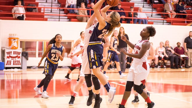 Players from Port Huron High School block Northern's Allie Sanderson as she jumps to shoot the ball during their game Dec. 8.