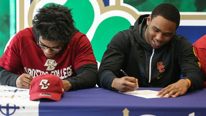 From left, Hugh Davis signs to play football at Boston College and Markese Stepp signs to University of Southern California at Cathedral High School, Indianapolis, Wednesday, Dec. 20, 2017.