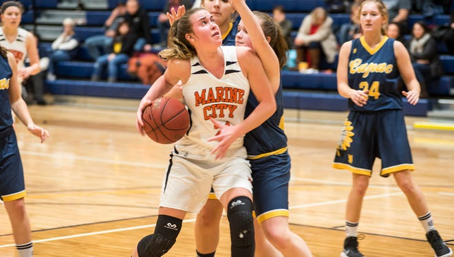 Players from Capac High School block Marine City's Stephanie Abraham (21) as she tries to shoot the ball during their SC4 Holiday Girls' Basketball Showcase match Dec. 28.