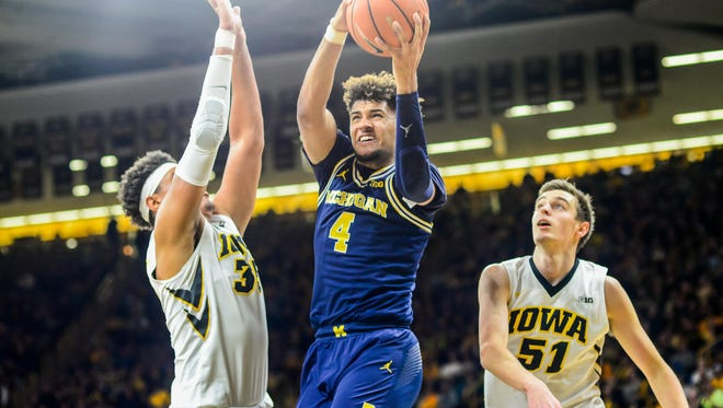 Michigan forward Isaiah Livers (4) controls the ball as Iowa forward Nicholas Baer (51) and forward Cordell Pemsl (35) defend during the second half of U-M's 75-68 win on Tuesday, Jan. 2, 2018, in Iowa City, Iowa.