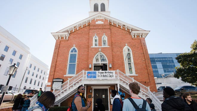 People stand outside Dexter Avenue King Memorial Baptist Church during their Martin Luther King Jr. Birthday Service on Monday, Jan. 15, 2018, in Montgomery, Ala.