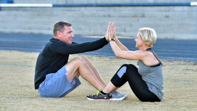 """Pete and Jen Gilroy, doing sit ups. High-Five Sit-Up:Begin by lying on the ground, knees bent and feet intertwined. In sync, each partner performs a sit-up, """"high-fiving"""" when they reach the top. Return to the starting position."""