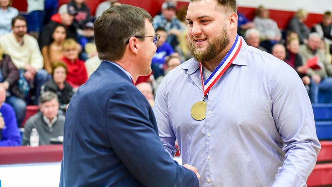 Former St. Clair High School football player Tim Lelito, right, shakes hands with athletic director Sandy Rutledge at the Hall of Fame induction ceremony at St. Clair High School Feb. 2. After graduating, Lelito went on to play in the NFL for the New Orleans Saints, the Tennessee Titans and the Detroit Lions.