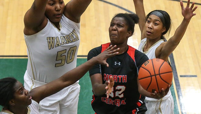North Central Panthers forward Nakaih Hunter (32) is surrounded by Warren Central Warriors defenders as she goes for a lay up during the second half of sectional finals between the Warren Central Warriors and North Central Panthers at Lawrence North High School in Indianapolis, Ind., Saturday, Feb. 3, 2018. Warren Central won, 66-54.