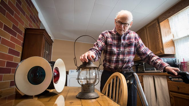 William Miskell talks in his Port Huron home Thursday about two railroad lamps that were given to him after the antique lamp that was mounted at the end of his driveway went missing. The donated lamps came after news about his lamp spread throughout the internet about two weeks ago.